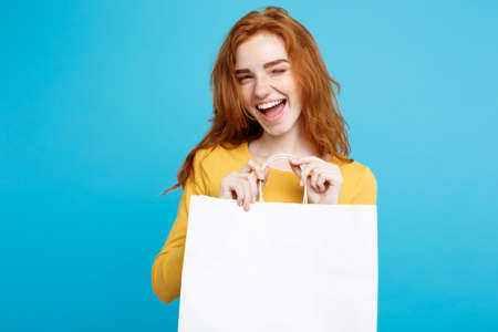 Conceito da compra - menina ascendente bonita nova próxima do redhair do retrato acima de sorriso olhando a câmera com saco de compras branco. Fundo Pastel Azul. Copie o espaço.