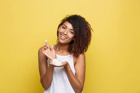 Beauty Concept - Beautiful young African American woman happy using skin care cream. Yellow studio background. Copy Space. Standard-Bild