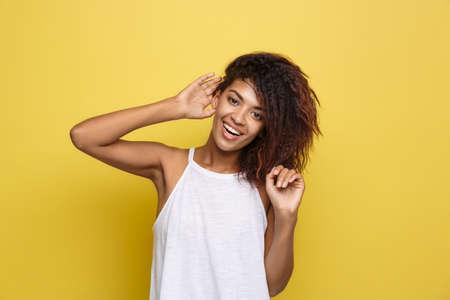 아름 다운 매력적인 아프리카 계 미국인 여자 게시 그녀의 곱슬 아프리카 머리와 재생. 노란색 스튜디오 배경입니다. 공간을 복사하십시오. 스톡 콘텐츠