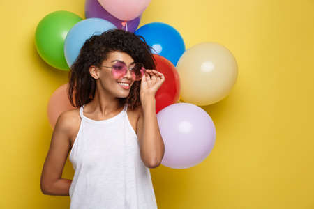 Celebration Concept - Close up Portrait happy young beautiful african woman with white t-shirt smiling with colorful party balloon. Yellow Pastel studio Background.