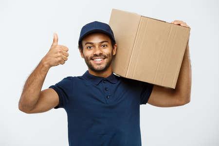 Leveringsconcept - Portret van de Gelukkige Afrikaanse Amerikaanse leveringsmens die een doospakket houden en dreunen omhoog tonen. Geïsoleerd op grijze studio achtergrond. Ruimte kopiëren.