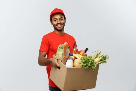 Concept de livraison - Handsome African American Delivery Man portant une boîte à colis d'épicerie et des boissons au magasin. Isolé sur fond de studio gris. Espace de copie. Banque d'images