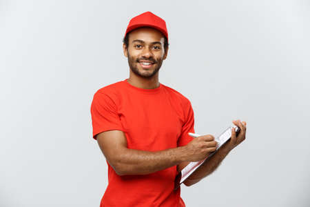 moving box: Delivery Concept - Portrait of Handsome African American delivery man or courier writing on a order document. Isolated on Grey studio Background. Copy Space.