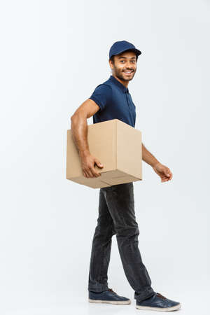 deliverable: Delivery Concept - Portrait of Happy African American delivery man in blue cloth walking to send a box package to customer. Isolated on Grey studio Background. Copy Space. Stock Photo