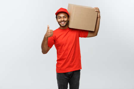 thumps up: Delivery Concept - Portrait of Happy African American delivery man holding a box package and showing thumps up. Isolated on Grey studio Background. Copy Space.