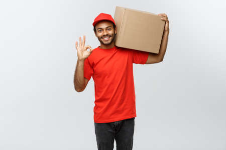 thumps up: Delivery Concept - Portrait of Happy African American delivery man holding a box package and showing ok sign. Isolated on Grey studio Background. Copy Space.