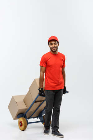 carretilla de mano: Delivery Concept - Portrait of Handsome African American delivery man or courier pushing hand truck with stack of boxes. Isolated on Grey studio Background. Copy Space.