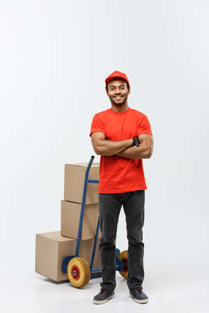 Delivery Concept - Portrait of Handsome African American delivery man or courier standing in front of hand truck with stack of boxes. Isolated on Grey studio Background. Copy Space.