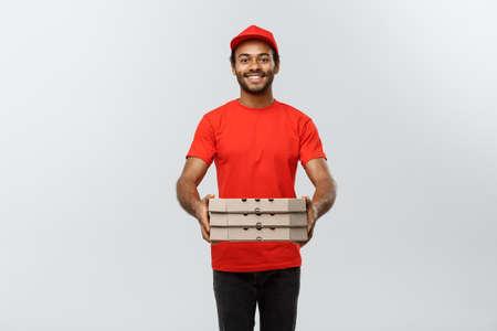 Levering Concept - Portret van knappe Afro-Amerikaanse Pizza bezorger. Geïsoleerd op grijze studio achtergrond. Ruimte kopiëren.