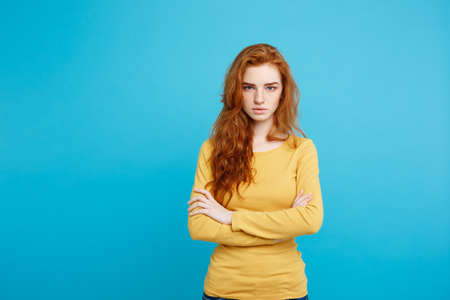 Portrait of young beautiful ginger woman with tender serious face crossing arms looking at camera. Isolated on pastel blue background. Copy space.