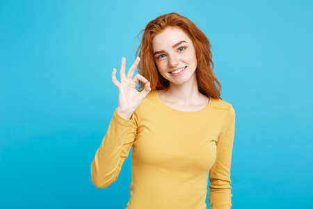 Fun and People Concept - Headshot Portrait of charming ginger red hair girl with freckles smiling and making ok sign with finger. Pastel blue background. Copy Space. Stock Photo