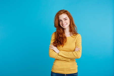Portrait of young beautiful ginger woman with freckles cheerfuly smiling looking at camera. Isolated on pastel blue background. Copy space.