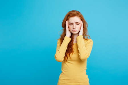 Healthcare Concept - Portrait of young beautiful ginger woman feeling sick and stressful. Isolated on pastel blue background. Copy space. Stock Photo