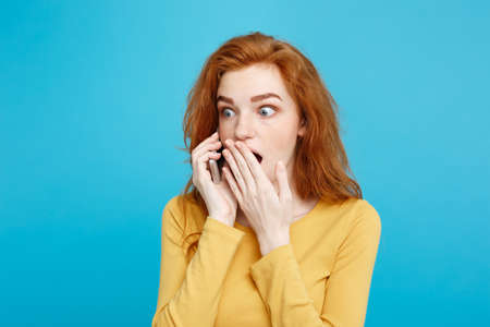 Lifestyle concept - Portrait of ginger red hair girl with shocking and stressful expression while talking with friend by mobile phone. Isolated on Blue Pastel Background. Copy space. 写真素材