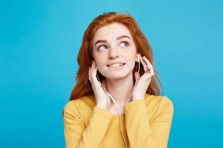 라이프 스타일 개념 - 쾌활 한 행복 생강 빨간 머리 소녀의 초상화 즐거운 미소를 카메라와 헤드폰을 함께 음악을 듣고 즐길 수 있습니다. 블루 파스텔