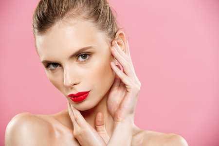 Beauty concept - Gorgeous Young Brunette Woman face portrait. Beauty Model Girl with bright eyebrows, perfect make-up, red lips, touching her face. Isolated on pink background