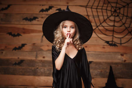 Halloween Witch concept - closeup shot of little caucasian witch child holding index finger at lips, asking to keep silence. Stock Photo
