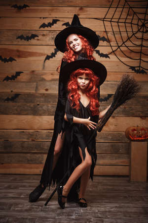 Halloween Concept - Beautiful caucasian mother and her daughter with long red hair in witch costumes celebrating Halloween posing with over bats and spider web on Wooden studio background.