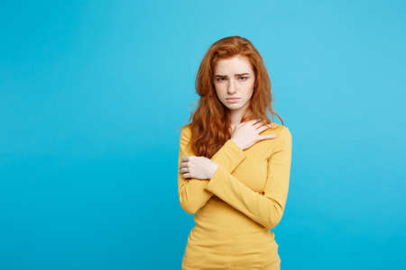Close up Portrait young beautiful attractive redhair girl feeling nervous looking at camera. Blue Pastel Background. Copy space. Stock Photo