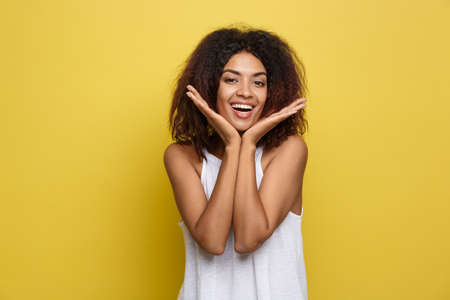 Smiling beautiful young African American woman in white T-shirt posing with hands on chin. Studio shot on Yellow background. Copy Space. Stockfoto