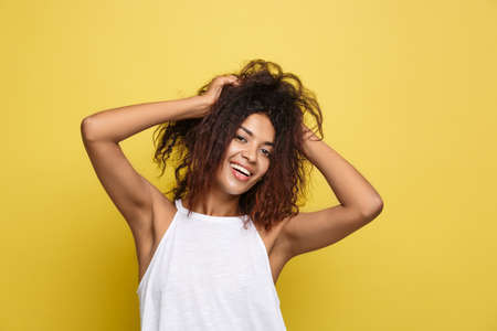 Beautiful attractive African American woman posting play with her curly afro hair. Yellow studio background. Copy Space. Imagens