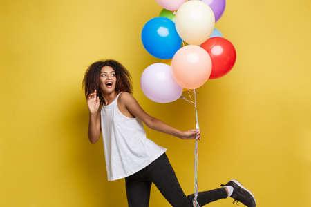 Concept de célébration - Close up Portrait heureux jeune belle femme africaine avec un t-shirt blanc en cours d'exécution avec un ballon de fête coloré. Fond de studio Pastel jaune