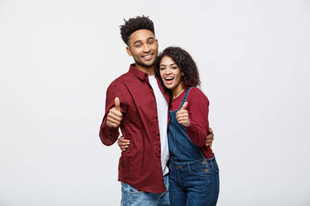 Portrait of attractive African american couple showing thumb up over white studio background. 스톡 콘텐츠