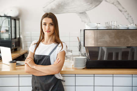 Coffee Business owner Concept - Portrait of happy attractive young beautiful caucasian barista in apron with confident looking at camera in coffee shop counter.