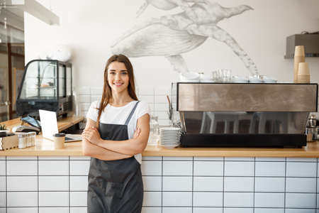 Coffee Business owner Concept - Portrait of happy attractive young beautiful caucasian barista in apron smiling at camera in coffee shop counter. Archivio Fotografico