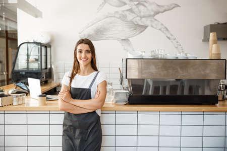 Koncepcja właściciela firmy kawy - Portret szczęśliwy atrakcyjny młody piękny kaukaski barista w fartuchu uśmiecha się do kamery w ladzie kawiarni.