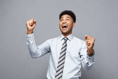 Business Concept - Confident happy young African American throwing fists in air celebrating for success projects.