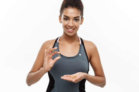 Healthy and Fitness concept - Closeup portrait of beautiful African American taking a pill of Cod liver oil. Isolated on white studio background.