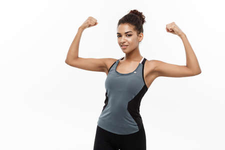 Healthy and Fitness concept - Portrait of young beautiful African American showing her strong muscle with confident cheerful facial expression. Isolated on white studio background.