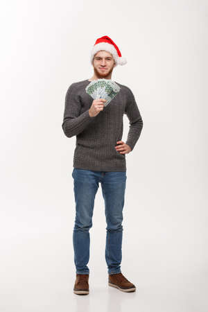 Holiday Concept - Young beard man in sweater showing money to camera. 版權商用圖片 - 96695609