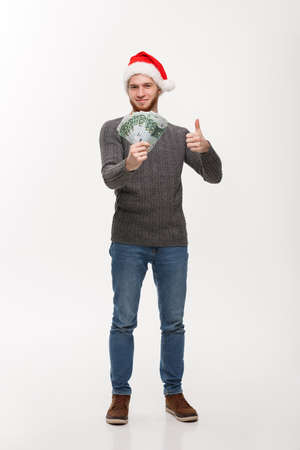 Holiday Concept - young beard man holding money in front over white background 版權商用圖片 - 96695704