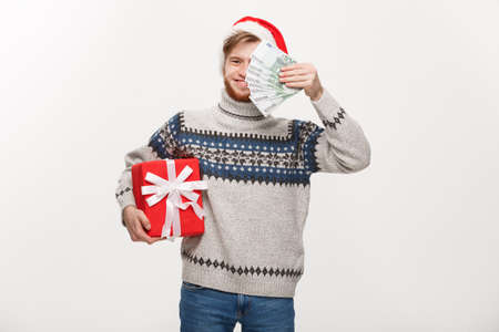 Holiday Concept - young beard man holding a christmas gift box and money over white background 版權商用圖片 - 96695708