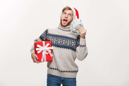 Holiday Concept - young beard man holding a christmas gift box and money over white background 版權商用圖片