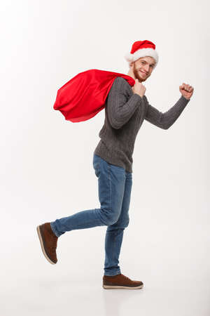 Christmas concept - Young confident beard man running and holding red big santa bag with a lot of present inside.