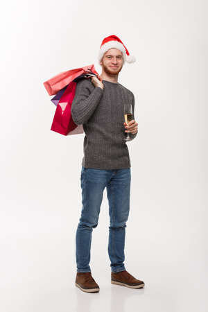 Christmas Concept - Young handsome beard man holding glass of champagne and shopping bags with happy facial expression.