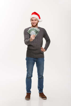 Holiday Concept - Young beard man in sweater showing money to camera.