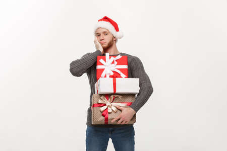 Christmas Concept - young handsome man with beard holding heavy presents with exhausted facial expression on white background. 免版税图像