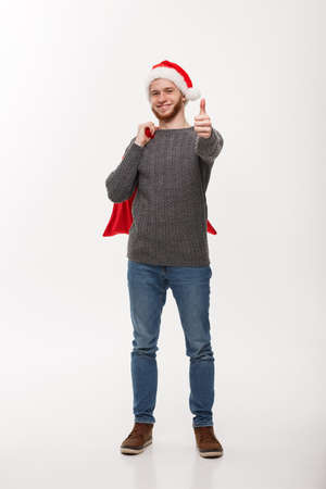 Christmas concept - Young confident smart man holding red big santa bag and giving thumb up.
