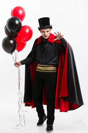 Full-lenght Portrait of handsome caucasian Vampire in black and red halloween costume. 免版税图像