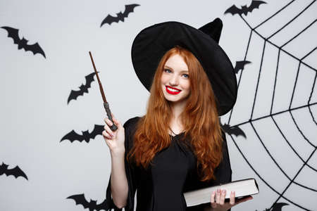 Halloween Concept - Beautiful Witch playing with magic stick on grey background. Stock Photo