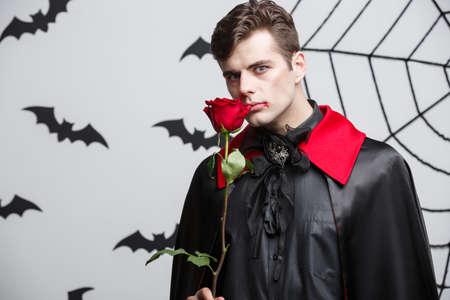 Vampire Halloween Concept - Portrait of handsome caucasian Vampire holding red beautiful rose. Stock Photo