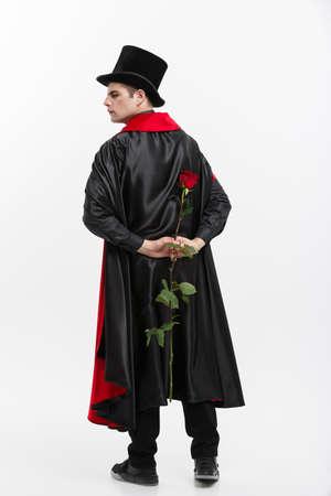 Vampire Halloween Concept - Portrait of handsome caucasian Vampire holding red beautiful rose on white studio background.