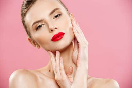 Beauty concept - Close up Gorgeous Young Brunette Woman face portrait. Beauty Model Girl with bright eyebrows, perfect make-up, red lips, touching her face. Isolated on pink background Stock Photo