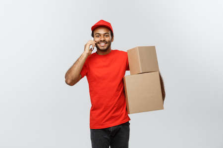 Delivery Concept - Portrait of Handsome African American delivery man or courier with box calling phone to customer. Isolated on Grey studio Background. Copy Space.