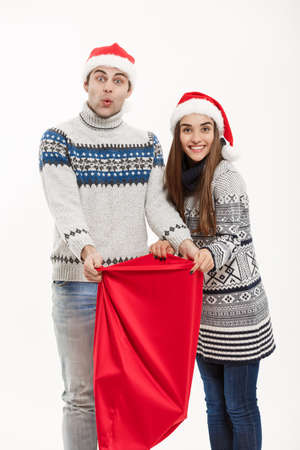 Chirstmas concept - young attractive couple with Santa red bag celebrating Chirstmas day. Isolated on White background Stock Photo