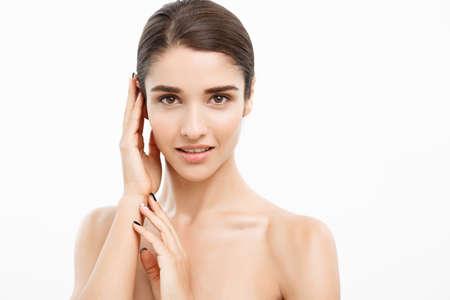 아름다움과 피부 관리 개념-가까이 흰색 배경에서 그녀의 피부를 만지고 아름 다운 젊은 여자.